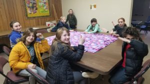 Children sit around a table upon which sits a flowered fleece blanket they are crafting. Students are looking at the camera and smiling.