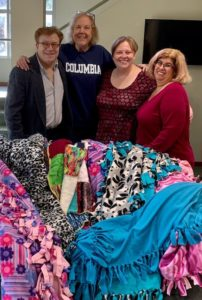 Three members of TBA staff stand with the regional Project Ezra coordinator behind colorful blankets that have been spread out over the sofa in the Temple lobby.