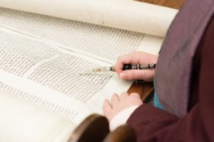 yad pointer in hand pointing to words on torah scroll